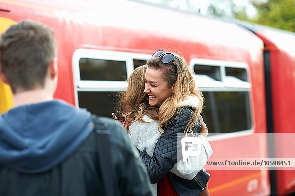 Two female friends hugging at railway station  smiling