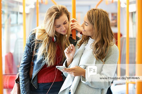 Two young female friends on train  looking at smartphone