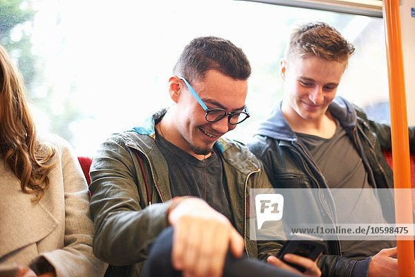 Two young male friends on train  looking at smartphone