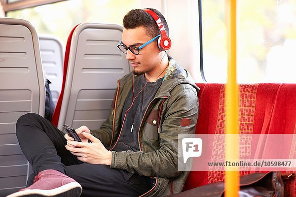 Young man sitting on train  using smartphone  wearing headphones
