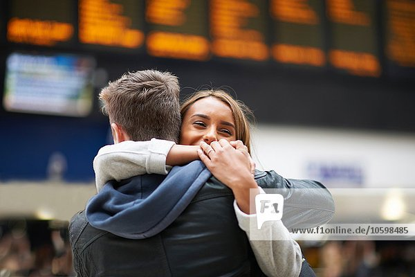 Heterosexual couple hugging at railway station  rear view