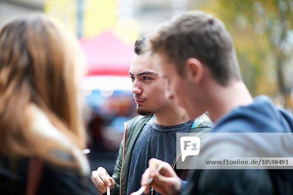 Group of young adults eating takeaway food  outdoors