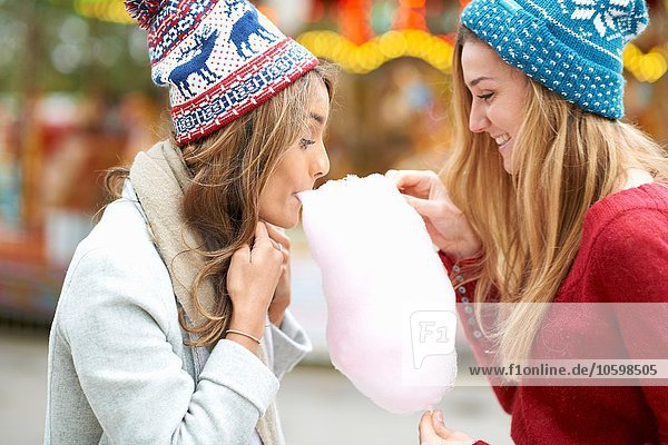 Two young women eating candy floss at funfair  outdoors