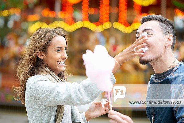 Young couple  fooling around  eating candy floss at funfair  outdoors