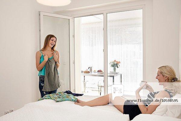 Frau  die auf dem Bett liegt und eine Kaffeetasse in der Hand hält  hilft dem Freund bei der Wahl des Outfits.