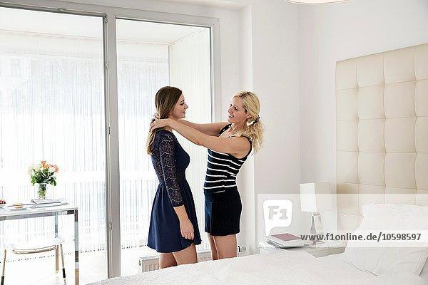 Seitenansicht der Frau im Schlafzimmer  die dem Freund im Kleid hilft  sich fertig zu machen.