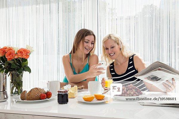 Frauen sitzen am Esstisch und genießen gemeinsam ein kontinentales Frühstück.