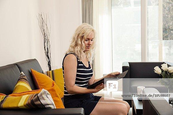 Seitenansicht einer reifen Frau  die auf einem Sofa sitzt und ein digitales Tablett hält.