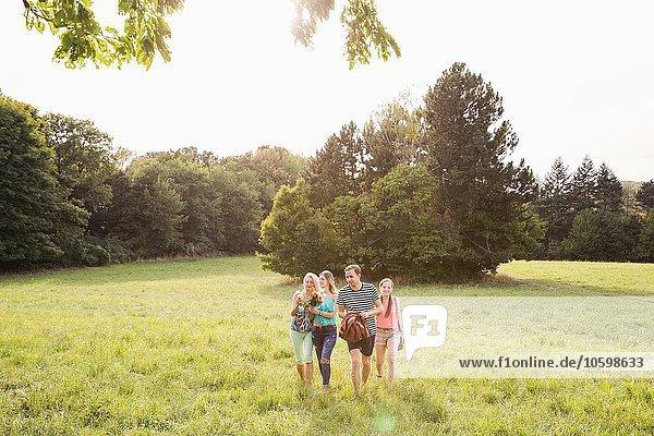 Vorderansicht der Familie mit Picknickdecke beim Spaziergang durch die Feldlandschaft