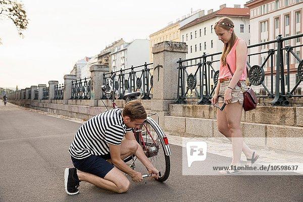 Junge Frau beobachtet jungen Mann beim Aufpumpen des Fahrradreifens