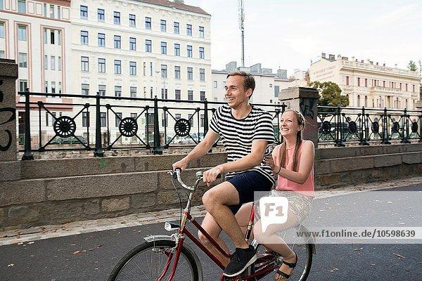 Junger Mann auf dem Fahrrad mit junger Frau auf dem Rücken sitzend lächelnd
