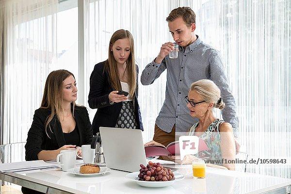 Kollegen am Tisch beim Frühstückstreffen mit Blick auf den Papierkram