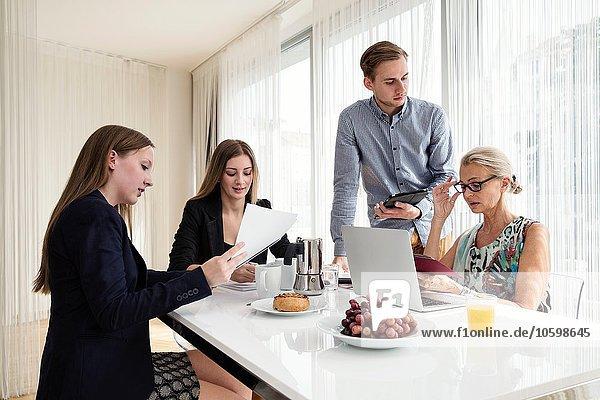 Kollegen  die an einem Tisch sitzen und digitale Tabletten und Papierkram beim Business-Frühstücksmeeting halten