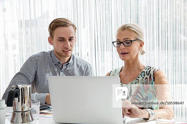 Kollegen sitzen und schauen auf Laptop-Computer