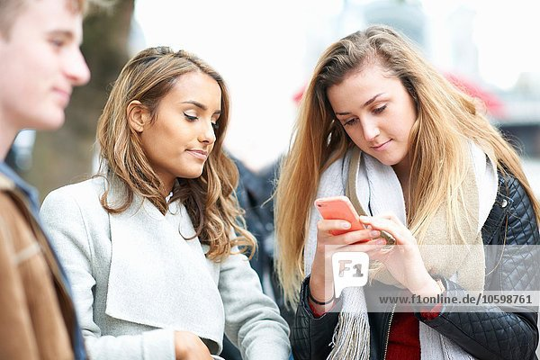Young woman with friends reading taking smartphone texts on street