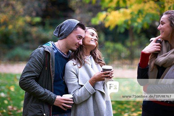 Junge erwachsene Freunde beim Plaudern und Kaffeetrinken im Herbstpark