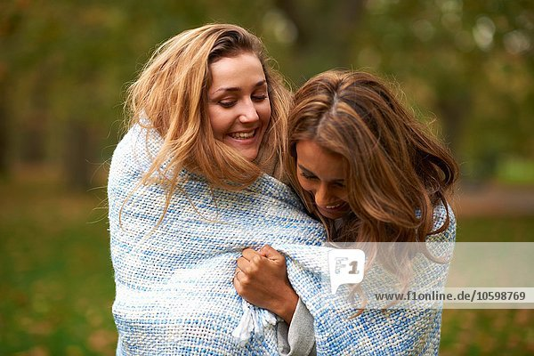 Two young female friends wrapped in blue blanket in park