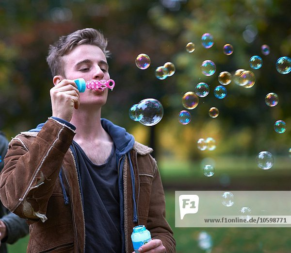 Young man blowing bubbles in autumn park