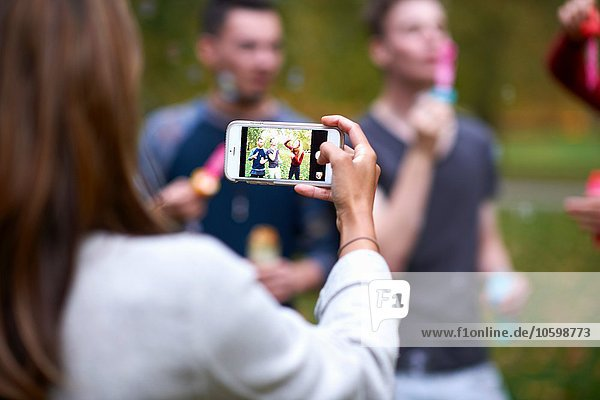 Over shoulder view of young woman taking smartphone photograph of friends in park