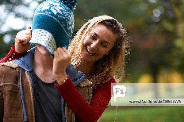 Young woman pulling knit hat over boyfriends face in park