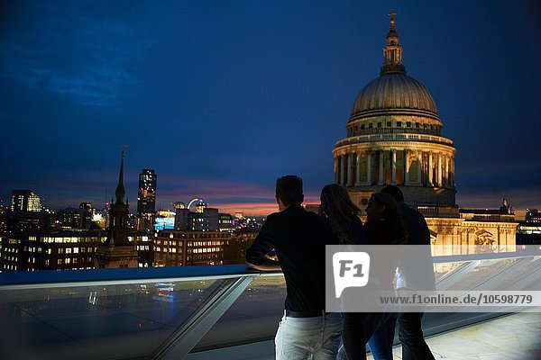 Silhouetted rear view of two young couples looking out to St Pauls at night  London  UK