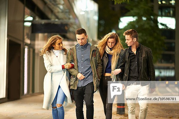 Two young couples strolling arm in arm on street at night  London  UK