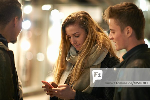 Young woman and friends reading smartphone texts on street at night  London  UK