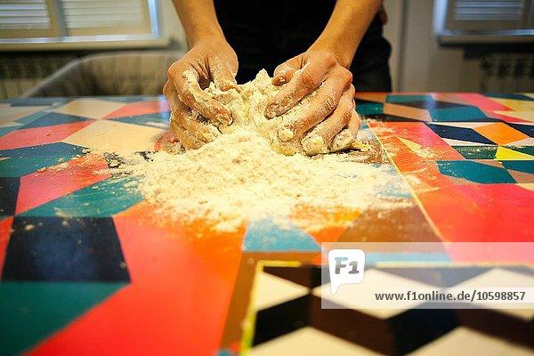 Nahaufnahme von Frauenhänden beim Teigformen auf dem Küchentisch