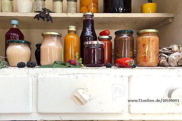 Gläser und Flaschen mit hausgemachten Speisen auf einem Küchenschrank im Retro-Stil