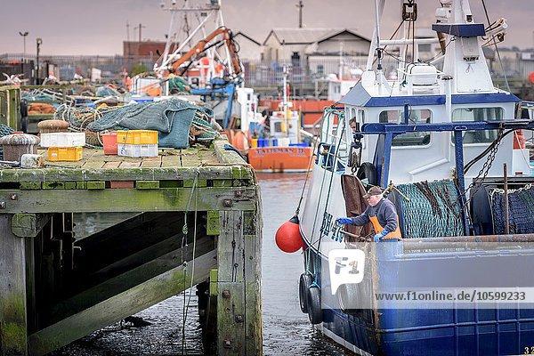 Fischer beim Anbinden von Trawlern im Hafen in der Abenddämmerung