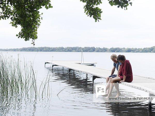 Paar sitzt auf dem Pier nebeneinander und taucht Zehen ins Wasser  Kopenhagen  Dänemark