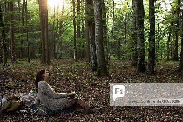 Seitenansicht einer reifen Frau  die im Wald auf einem Picknickteppich sitzt und eine Kaffeetasse mit Blick in die Ferne hält.