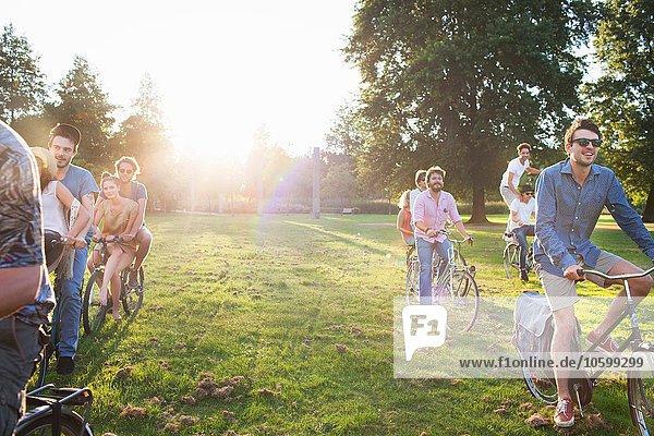 Reihen von Erwachsenen  die bei Sonnenuntergang mit dem Fahrrad im Park ankommen.