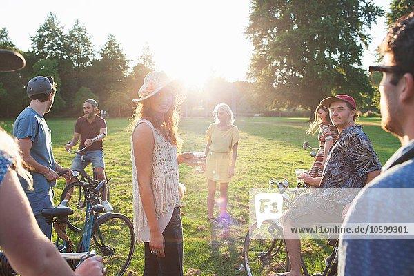 Gruppe von Erwachsenen  die bei Sonnenuntergang mit dem Fahrrad im Park ankommen.