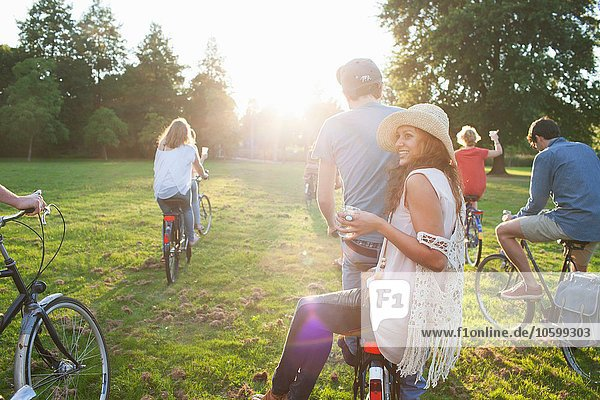 Rückansicht der Party für Erwachsene im Park auf Fahrrädern bei Sonnenuntergang