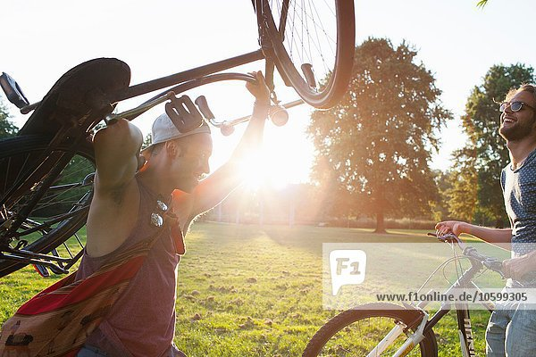 Two male friends arriving in park with bicycles at sunset