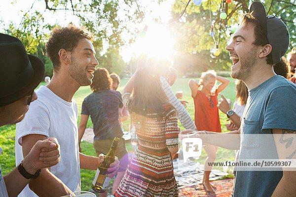 Gruppe erwachsener Freunde beim Plaudern auf der Party im Park bei Sonnenuntergang