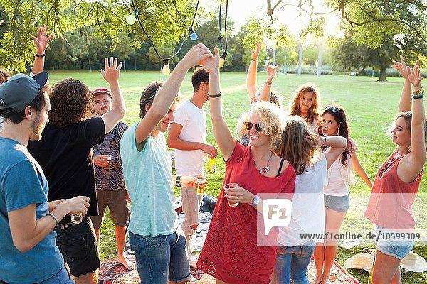 Eine Menge erwachsener Freunde tanzt auf einer Party im Park bei Sonnenuntergang.