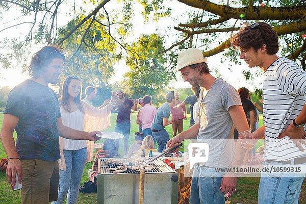 Fröhliche erwachsene Freunde beim Grillen bei Sonnenuntergang im Park
