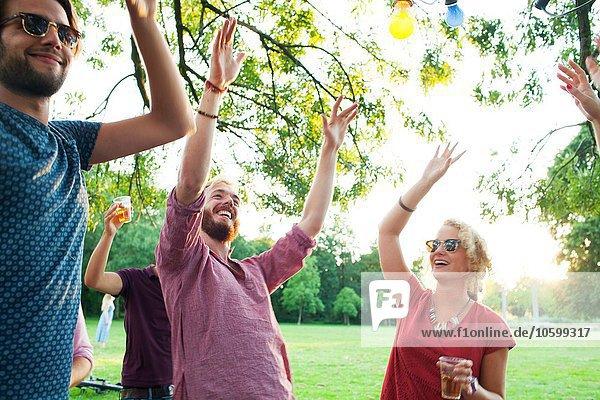 Erwachsene Freunde tanzen mit erhobenen Armen bei Sonnenuntergang Party im Park