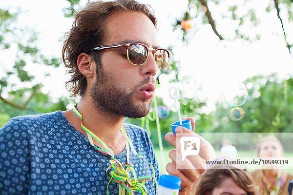 Junger Mann bläst Blasen bei Sonnenuntergangsparty im Park