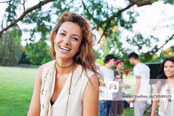 Porträt der glücklichen jungen Frau bei Sonnenuntergang im Park
