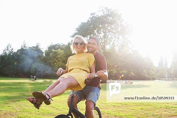 Porträt eines jungen Paares mit Spaß am Fahrrad bei der Sonnenuntergangsparty im Park