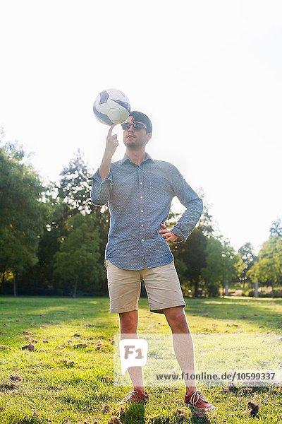 Porträt eines jungen Mannes beim Drehen eines Balls im sonnenbeschienenen Park