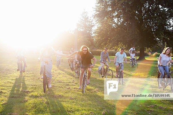 Massen von erwachsenen Freunden  die mit dem Fahrrad zum Sonnenuntergang anreisen.