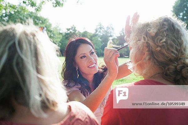 Weibliche erwachsene Freunde  die sich bei der Sunset Park Party schminken.