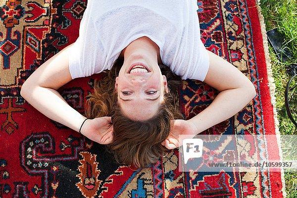 Draufsicht auf eine junge Frau  die auf einem Teppich liegt.