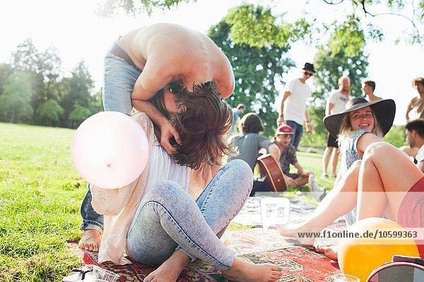 Junger Mann  der sich nach vorne beugt  um seine Freundin auf der Parkparty zu küssen.