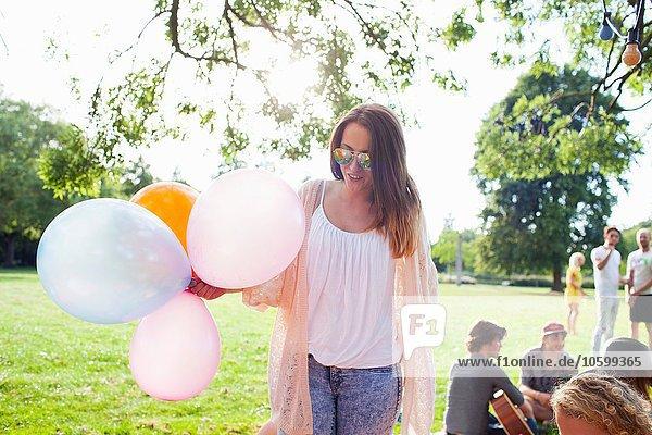 Junge Frau mit Luftballons auf der Parkfeier