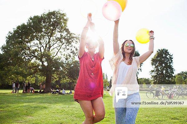 Zwei junge Frauen tanzen mit Luftballons auf der Parkparty
